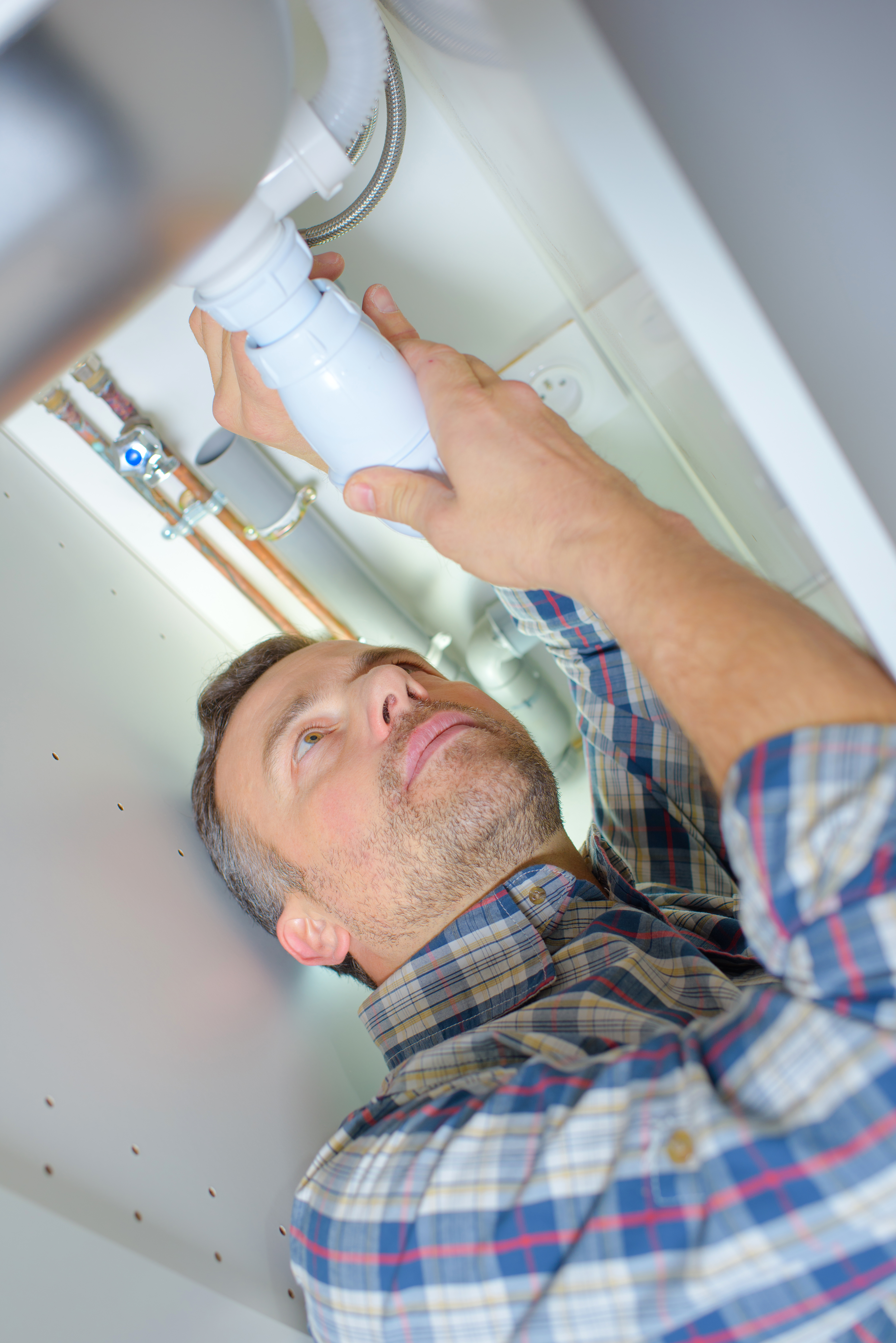 Plumber working on a plastic pipe